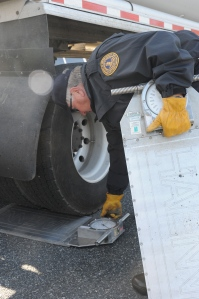 John Griffin, Department of Motor Vehicles, Size and Weight Compliance agent, sets portable scales in place for a motor carrier weight inspection.