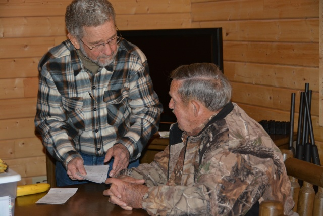 Steve Delovich, AUSA, and Russell Harvey, Pop's Shop, review the check cards that the hunters will take home with their processed deer meat.