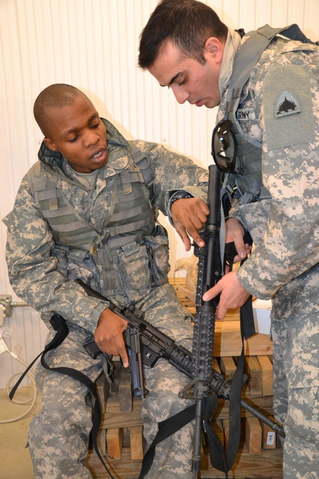 Army Spc. Hilary Kiundi and Army Spc. Arsham Orami familiarize themselves with the M4 rifle