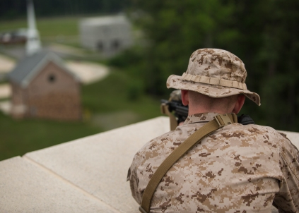 A Marine assigned to a Marine Security Augment Unit posts security on the rooftop of a simulated embassy building during embassy reinforcement training at the Asymmetric Warfare Training Center at Fort A.P. Hill, Va., June 27, 2016, as part of a certification exercise for the unit's upcoming deployment in support of Special-Purpose Marine Air-Ground Task Force, Crisis Response-Africa. During the training, the unit learned the most effective way to handle situations involving violent local citizens and what it feels like to interact with a combative local populace. (U.S. Marine Corps photo by Sgt. Michelle Reif/Released.)