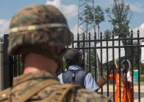 A Marine with Fox Company, 2nd Battalion, 8th Marine Regiment posts security inside a simulated embassy gate while an unruly mob of local civilian role players protests during embassy reinforcement training at the Asymmetric Warfare Training Center at Fort A.P. Hill, Va., June 28, 2016, as part of a certification exercise for the unit's upcoming deployment in support of Special-Purpose Marine Air-Ground Task Force, Crisis Response- Africa. During the training, the unit learned the most effective way to handle situations involving violent local citizens and what it feels like to interact with a combative local populace. (U.S. Marine Corps photo by Sgt. Michelle Reif/Released.)